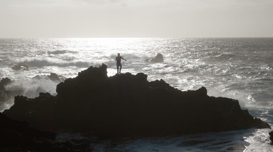 Man climbing the vulcanic rocks of Azores