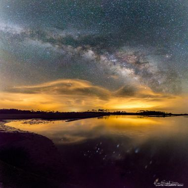 Lower Suwannee NWF, Florida, USA.  A severe thunderstorm rumbles under the Milky Way several miles in the distance beyond Shell Mound near Cedar Key.    The lightning creatively illuminated the clouds, the horizon and the foreground with cool reflections in the water   This square panoramic composition is made up of 30 individual exposures, each taken horizontally at ISO6400, 16mm, F2.8, 20 seconds - then stitched together using Lightroom CC.