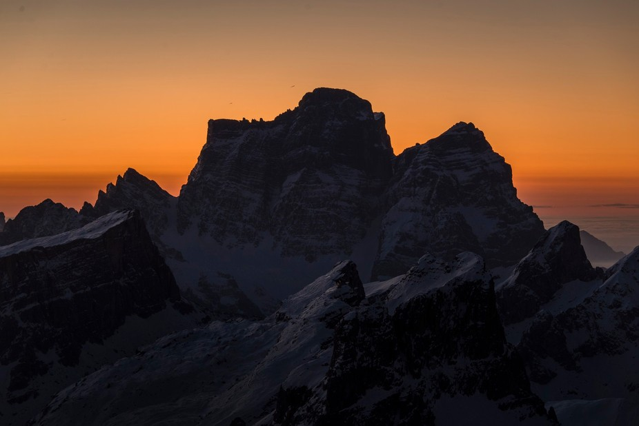The sun rises behind Monte Pelmo as seen from the Lagazuoi summit.