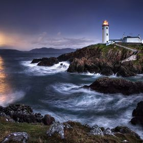 Fanad Head lighthouse in Co Donegal Ireland. Captured at dusk with the warm tones of the rising moon casting its light over a turbulent sea.