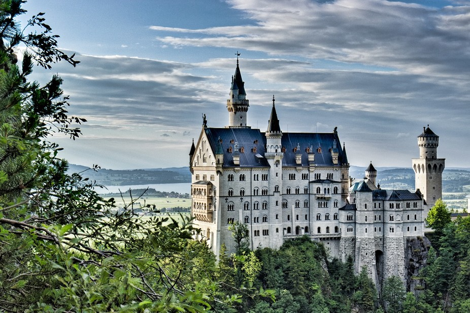 Neuschwanstein Castle is a nineteenth-century Romanesque Revival palace on a rugged hill above th...
