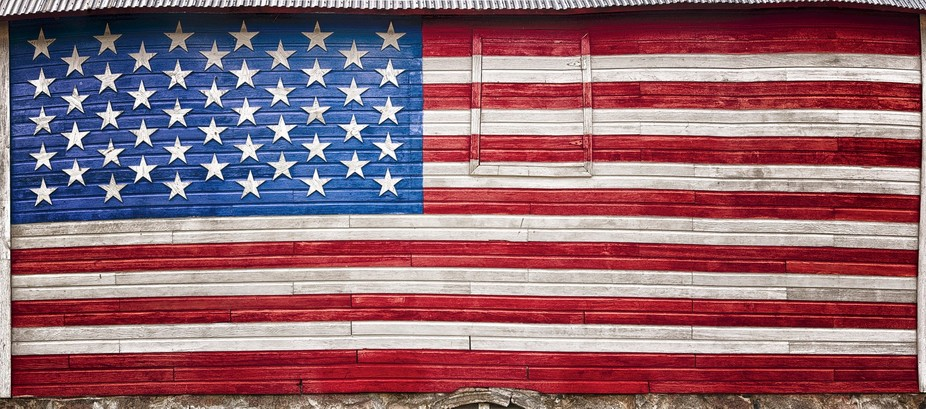 US flag painted on the side of an old barn.