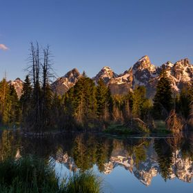 Sunrise paints the eastern face of the Teton Range as it is reflected in the beaver pond at Schwabacher's Landing in Grand Teton National Park.