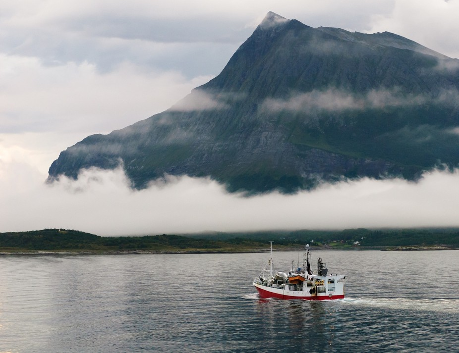 Early morning a fishing vessel heads out as the mist hangs low at the edge of the mountain