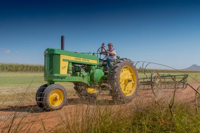 Farmer Brown on his green John Deere tractor on a dusty road.