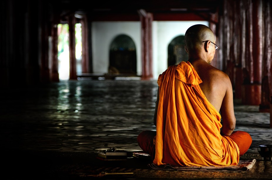 A monk in meditation under a temple Mandalay, Myanmar