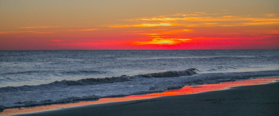 A caption of a colorful sunset on the North Carolina shoreline. The reflection on the surf made this shot irresistible.
