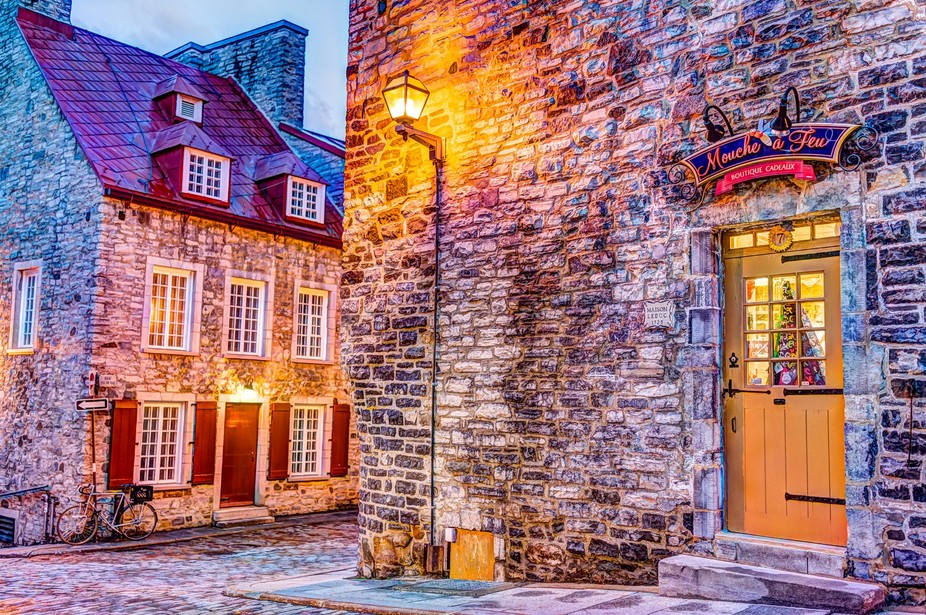 Colorful stone buildings on street during twilight in lower old town with Mouche a Feu boutique