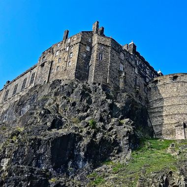 I took this photo when me and my family were in Edinburgh, Scotland in the year 2014. We were walking around Edinburgh looking at shops and taking photographs of the surroundings and we came to a spot where the Edinburgh Castle was towering above us. So, I took this shot.
