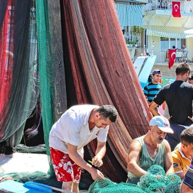 I took this photo when me and family went to Anadolu Kavağı in İstanbul, in the year 2012. I noticed fihermen repairing their fishing nets, so I took this photo.