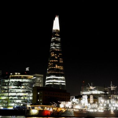 The shard at night in London with the ship HMS Belfast below.
