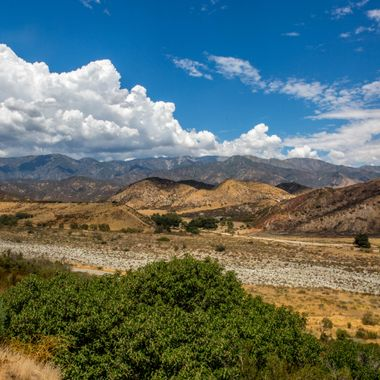 A summer desert view looking north across the San Gorgonio dry river bed toward the San Bernardino mountains in Southern California.