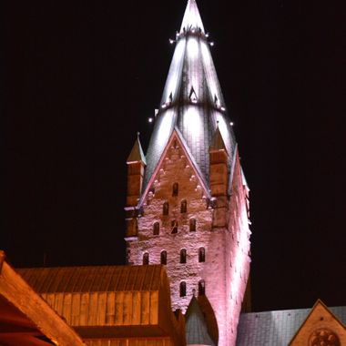 The illuminated Dom Clock tower in Paderborn.