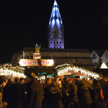 Xmas market with the Dom clock tower illuminated in the background.