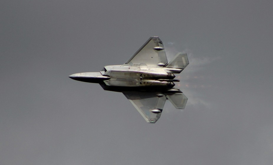A F22 raptor in plan view with full afterburner and vapour trails.