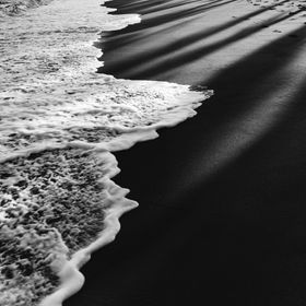 Black and white photo of a black sand beach detail; waves washing ashore with palm tree shadows over the sand