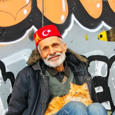 I took this photo when me and family were in Istanbul, in the year 2015. He was sitting at the side of one of the busiest shopping street in Istanbul (Istiklal Caddesi, Beyoglu) with his cat and he gave me permission to take this photo.