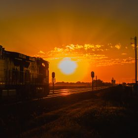 A westbound empty coal train has the green signal through Overton, Nebraska as the sun calmly sets in the distance.