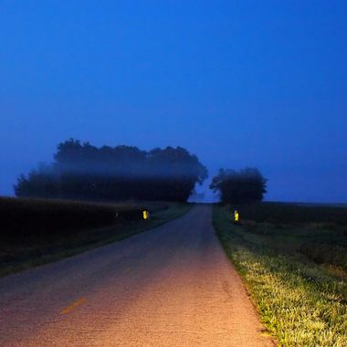 Fog rolling across the road early in the morning, before the sunrise.