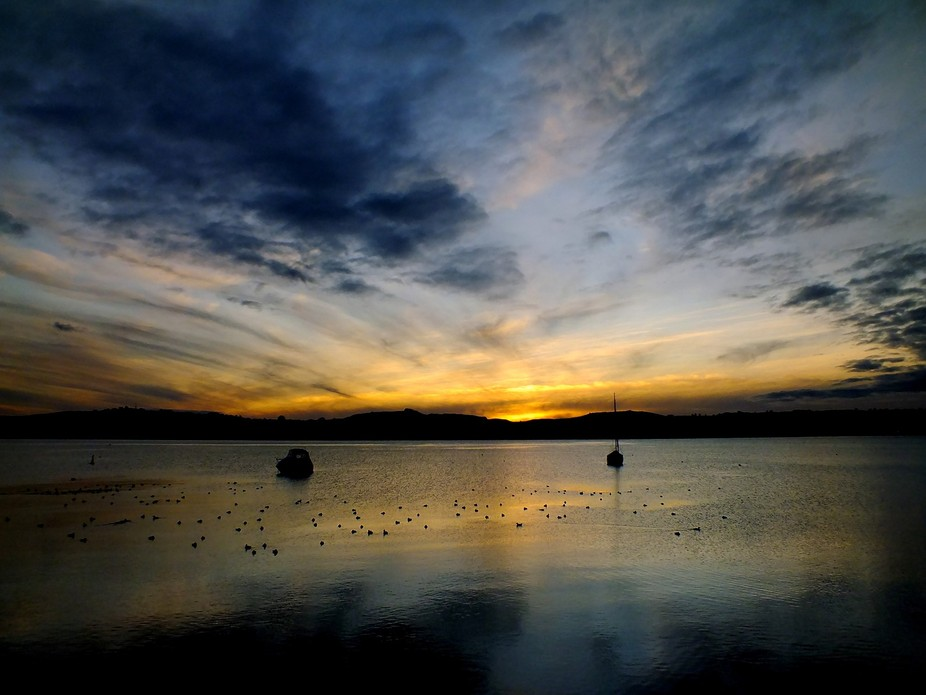 The sun sets on a glass calm Lake Taupo in New Zealand.