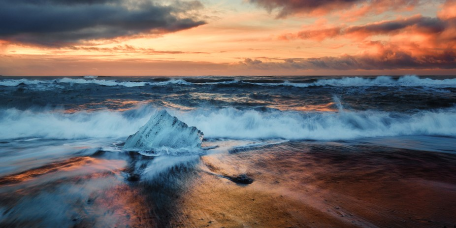Backwash from waves on a black sand beach glows with the pre-sunrise dawn colors as it hits ice c...