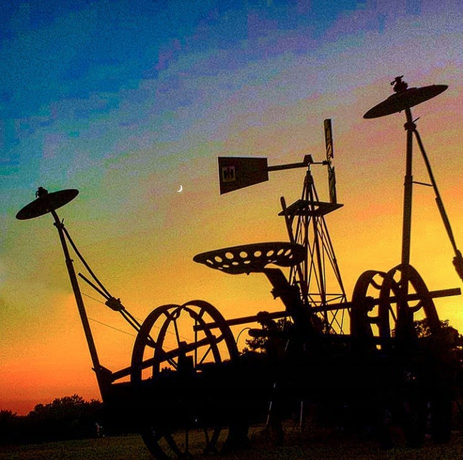 Antique mule farming equipment with a windmill and the beautiful sunset in the back