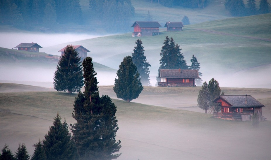 Lodges into a foggy sunrise in Seiser All, Dolomites