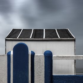 A blue concrete fence and a cabin on the beach ...