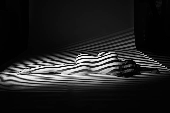 The model was lit using a single compact strobe with a light blaster and a metal gobo, creating the stripes of light and shadow. Model: Leo Johanna (Model Mayhem # 775409)  http://www.modelmayhem.com/LeoJohanna 20161006 228b