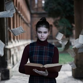 A girl with a book and a cold look. Around her pages flew out of the book against the backdrop of the old university. Concept: stopping time.