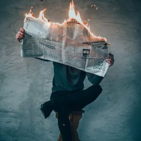 A man reads a newspaper in fire. Concept: self reflection