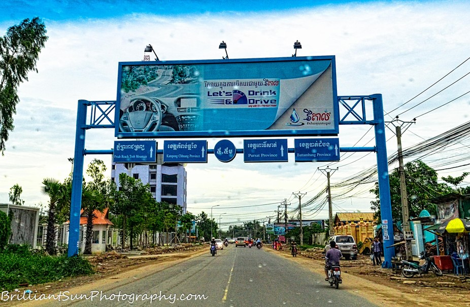 "The sign says, ""Let's Drink & Drive"". My initial thought was, no wonder people in Cambodia drive so wild. I later realized that it was a billboard ad for a bottled water company and the people here just don't know how to drive."