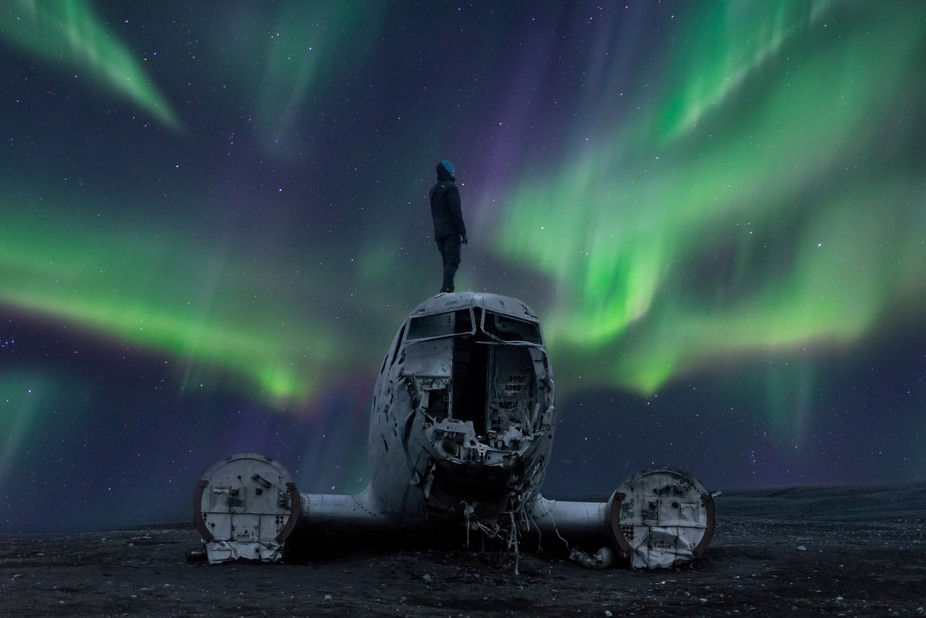 The northern lights dance above the famous DC3 wreckage located on Iceland's South coast.