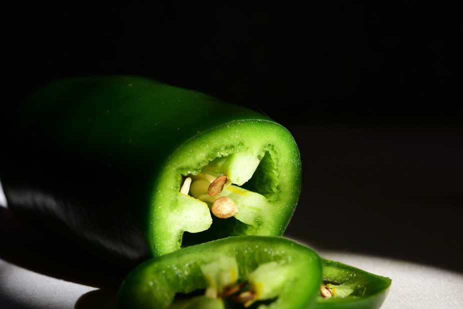 Portrait of a jalapeno pepper on the kitchen counter. Hand-held, natural light.