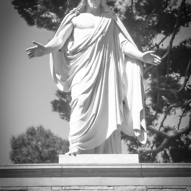 Went to a funeral at Forest Lawn in Orange County. Wandered around for a little while before the services, and something in me told me to bring the big camera, yet I didn't. This is a picture of a statue of Jesus out in one of the burial grounds that I found. He's about 15 feet up in the air up above the actual burial area on a wall looking down upon all the grave markers. Absolutely stunning statue. Unfortunately, I didn't have the Canon with me, but I was able to take a halfway decent picture of it with the smart phone. Black and White rendering of the color photograph.
