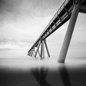 long exposure in b&w of a pier running into the ocean