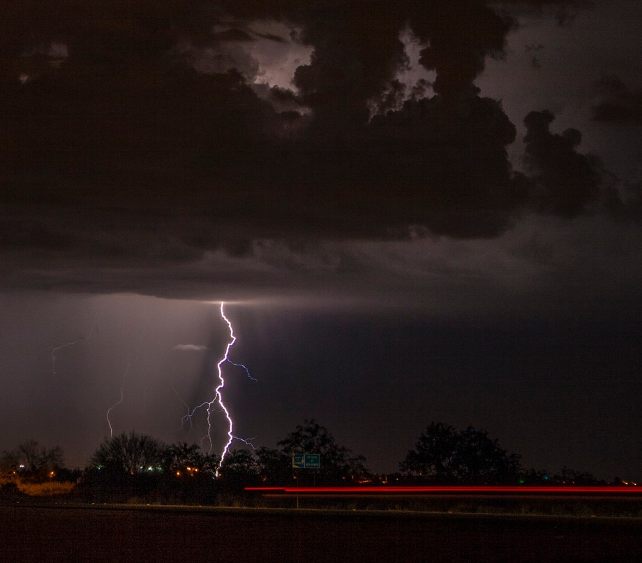 A solo lightning strike with a rain shower next to it