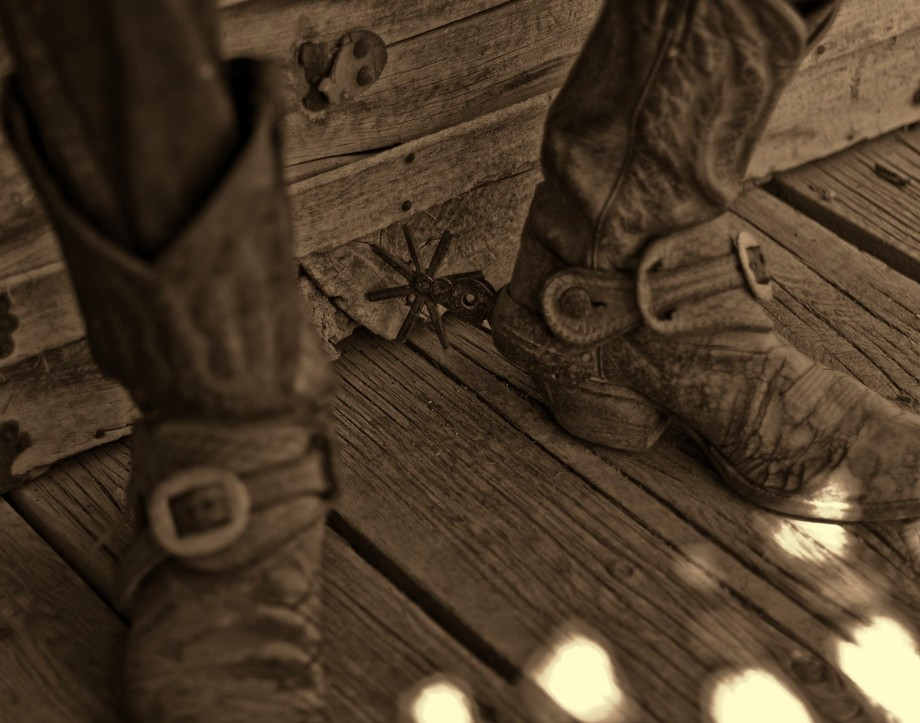 spurs in old sepia tone with a real old and worn cowboy boots, not to mention the cowboy.