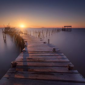 An old peer in a litlle village of Portugal.  The sun, the wooden dock and the water makes this picture a magical place