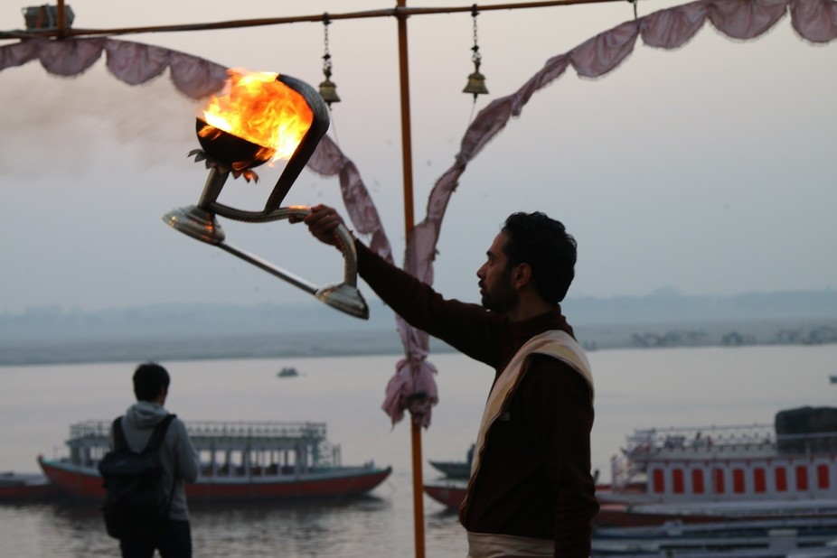 A priest in India using fire to pray.