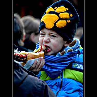 Boy eating a very hot Bratwurst in Germany.