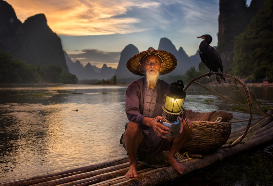 Old fisherman and his cormorant ln Li River - China