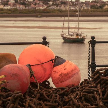 Floats and Chains at Conwy Harbour with a yacht in the River Conwy.