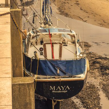 A yacht moored alongside the Quay at Conwy Harbour at low tide.