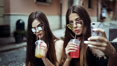 Two cute girls are drinking cold fruit drinks