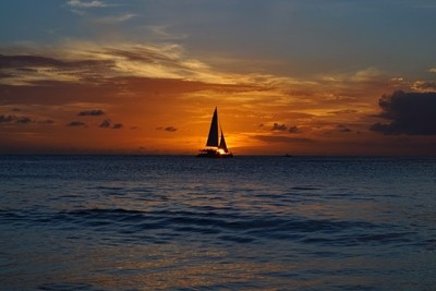 Sailing boat silhouette through  sunset