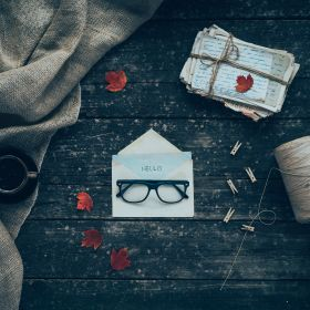 Welcome letter with glasses on old wooden board and red leaves. Conception: Hello fall.