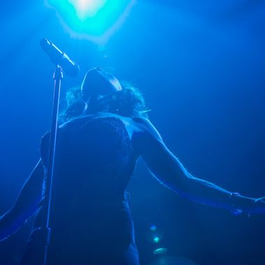 Tina Arena onstage, bathed in blue light, at The Plenary, Melbourne, during her Innocence to Understanding Tour.