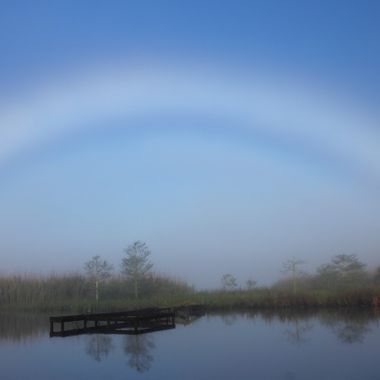 Known as a white rainbow or a fog-bow, this weather phenom is created by tiny water droplets that cannot produce the prism effect. Normally occurs in the Arctic or the mountains. This is Venice, LA.