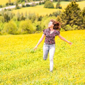Young woman running, jumping in air and smiling on countryside yellow dandelion flower fields in summer grass in Ile D'Orleans, Quebec, Cana...